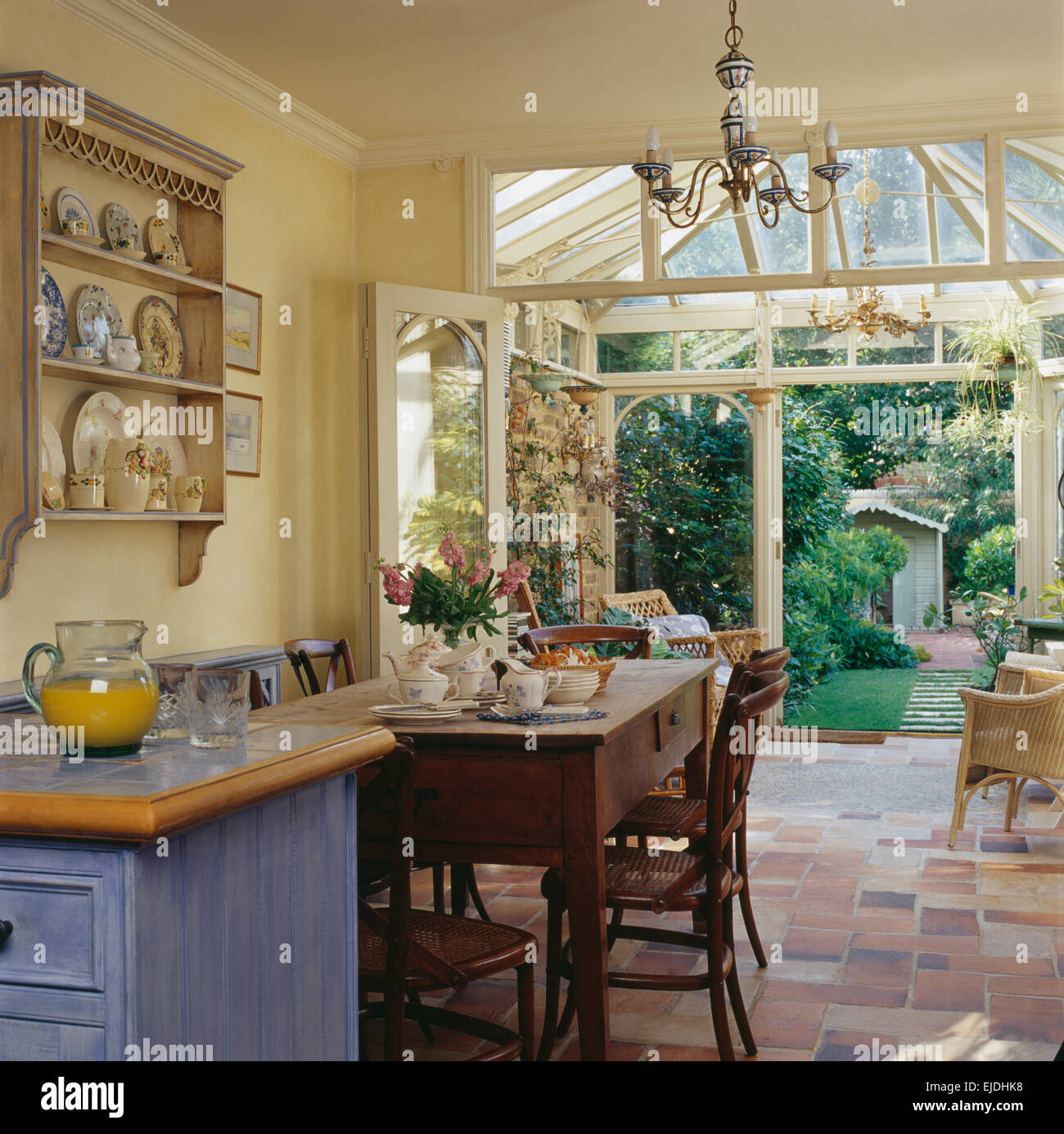 Simple Wooden Table And Chairs In Country Kitchen Dining Room With  Conservatory Extension And Doors Open To The Garden