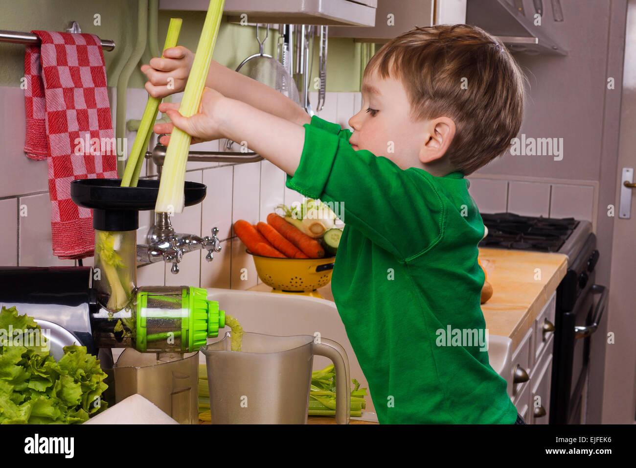 Little boy making green juice - Stock Image