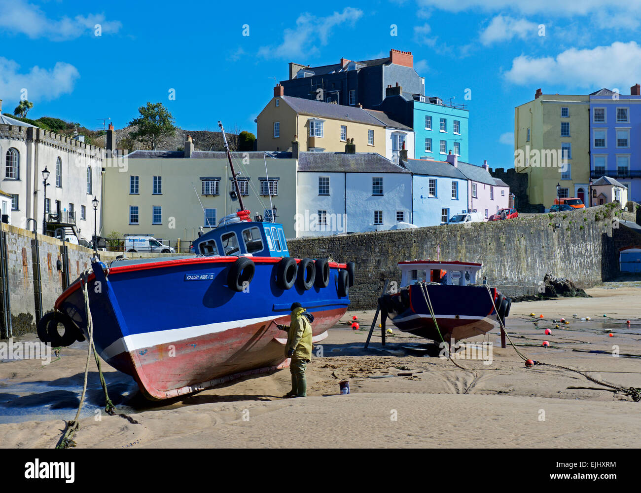 man-painting-fishing-boat-on-the-beach-in-tenby-harbour-pembrokeshire-EJHXRM.jpg