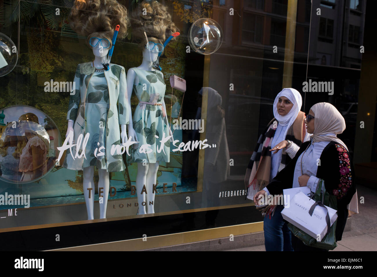 Two Muslim women walk past a display of eccentric mannequins in diving masks and snorkels, outside a central London Stock Photo