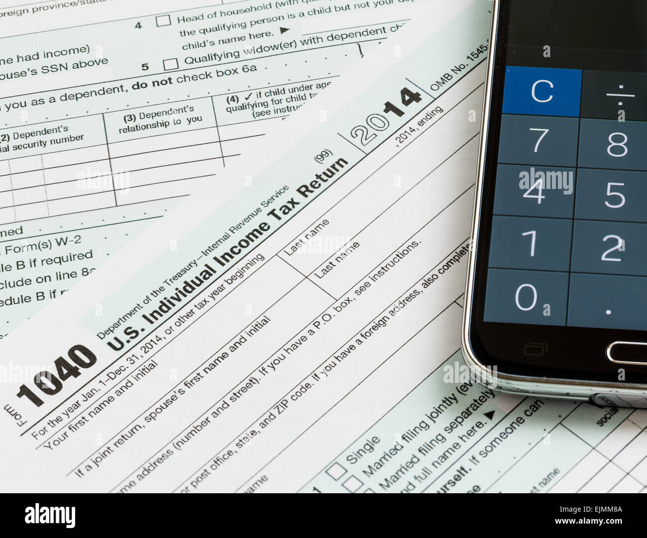 USA tax form 1040 for year 2014 with calculator app on smartphone ...
