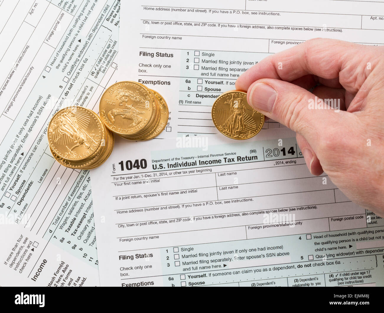 Caucasian Hand Counting Solid Gold Eagle Coins On Usa Tax Form 1040
