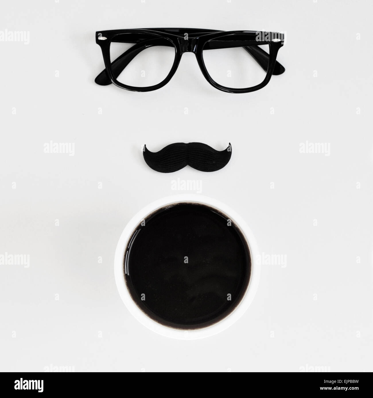 high-angle shot of a white table with a pair of black plastic-rimmed eyeglasses, a fake moustache and a cup of coffee, - Stock Image