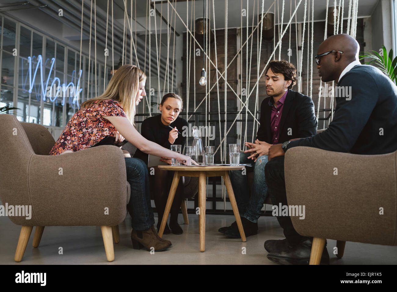 Diverse group of executives meeting in office sharing creative ideas. Young people having a meeting in lobby. - Stock Image