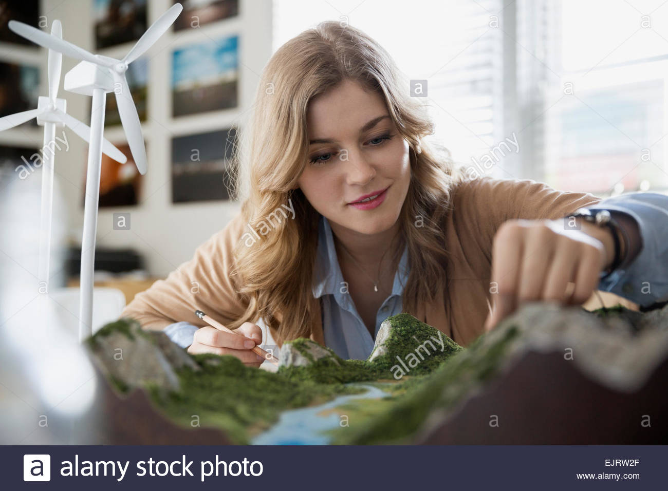 Engineer assessing wind turbine and landscape models - Stock Image