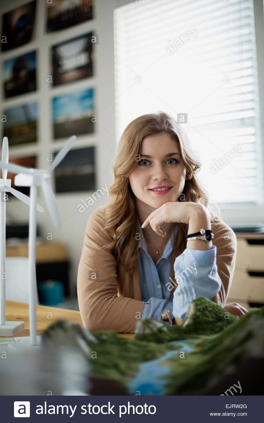 Portrait of confident engineer with wind turbine models - Stock Image