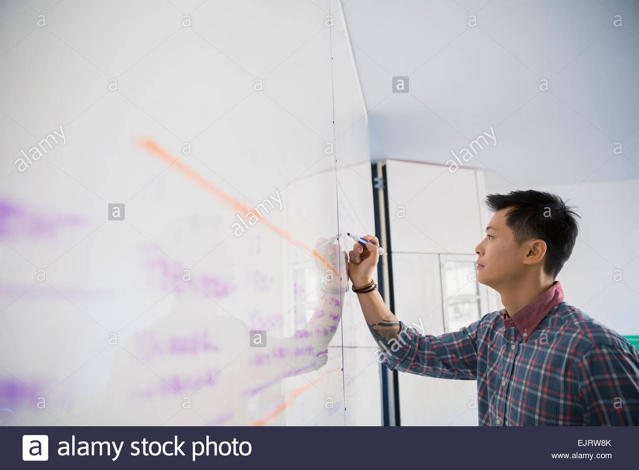 Businessman writing on whiteboard Stock Photo