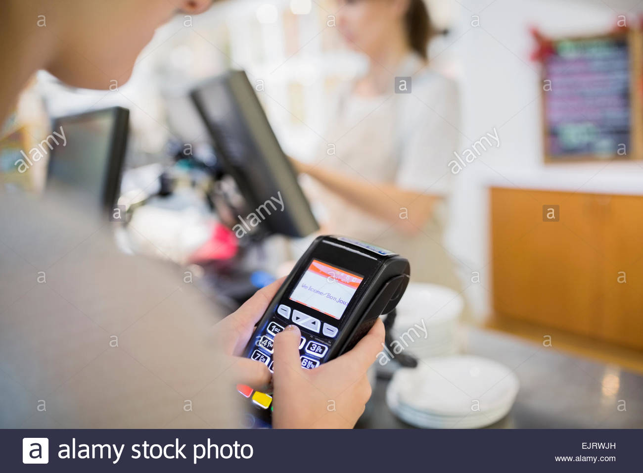 Woman using credit card reader in cafe - Stock Image