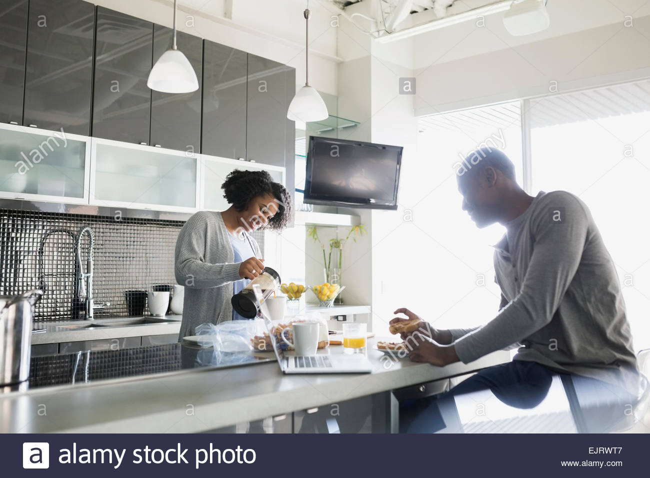 Couple with coffee at breakfast bar in kitchen - Stock Image