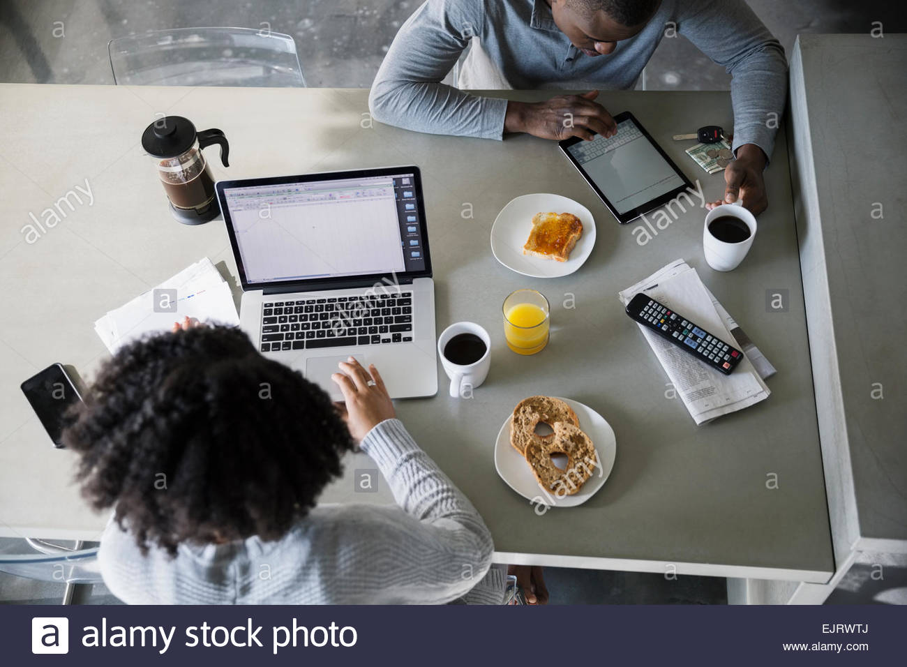 Overhead view of couple with technology in kitchen - Stock Image