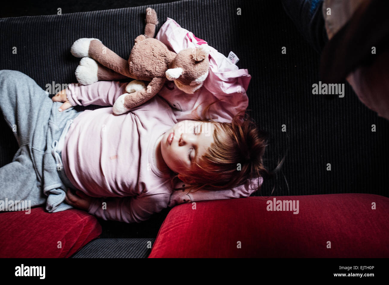 High angle view of baby sleeping in train - Stock Image