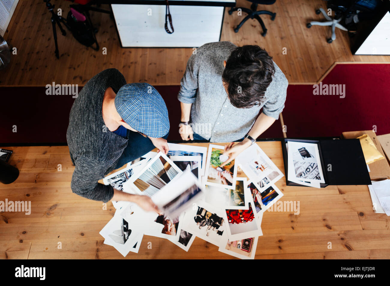 High angle view of businessmen analyzing photographs at desk in office - Stock Image