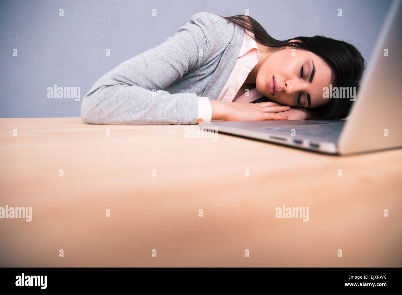 Young pretty woman sleeping on the table with laptop - Stock Image