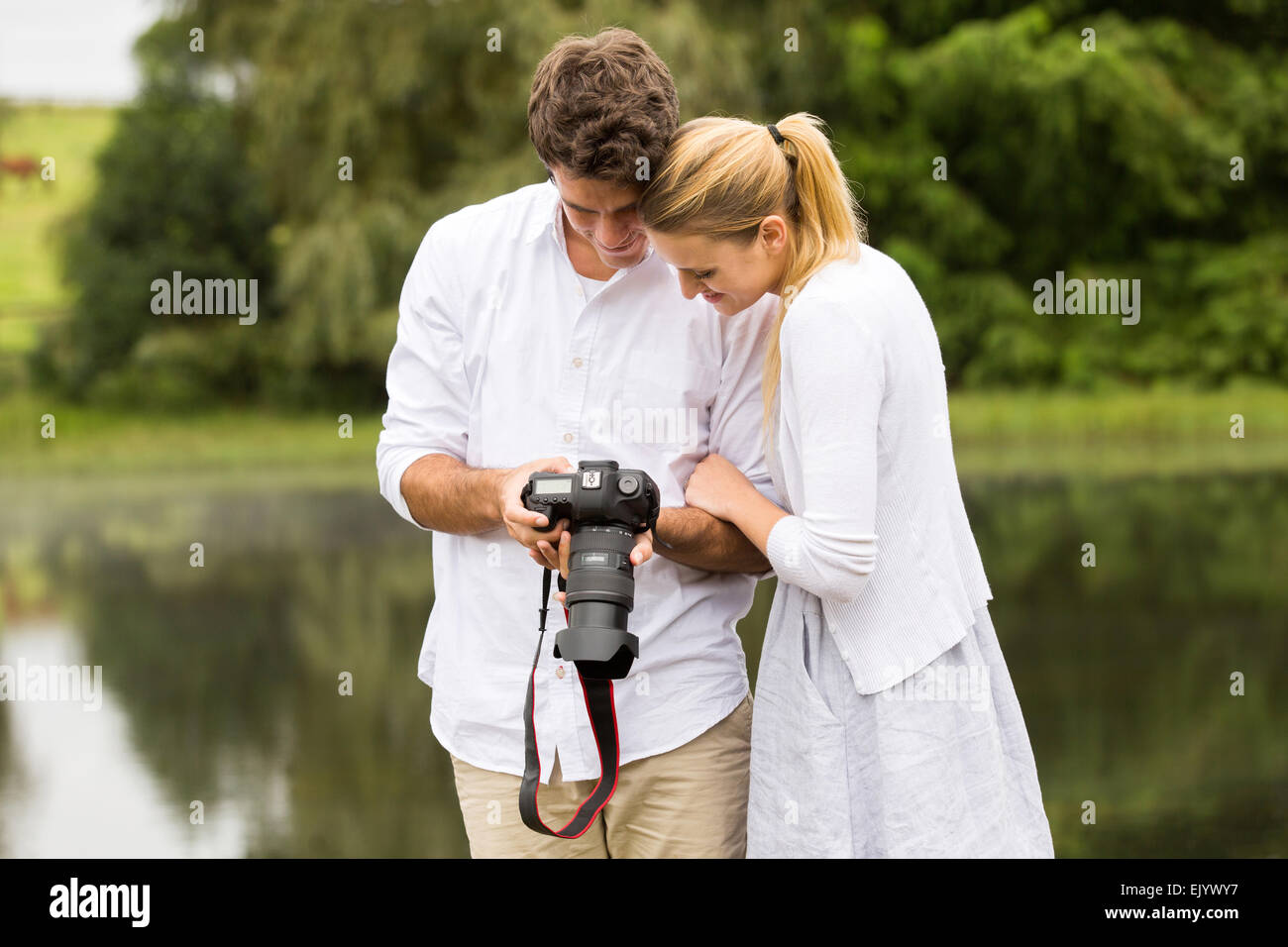 happy young couple viewing pictures on camera outdoors - Stock Image