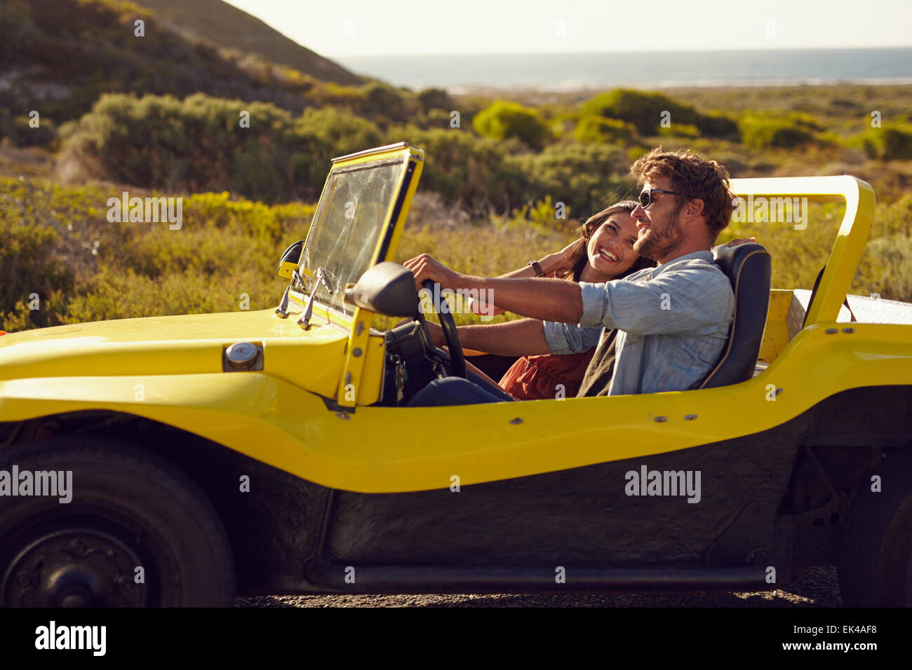 Smiling couple going on holidays together on a summer day. Young man with his girlfriend on  road trip in a buggy - Stock Image