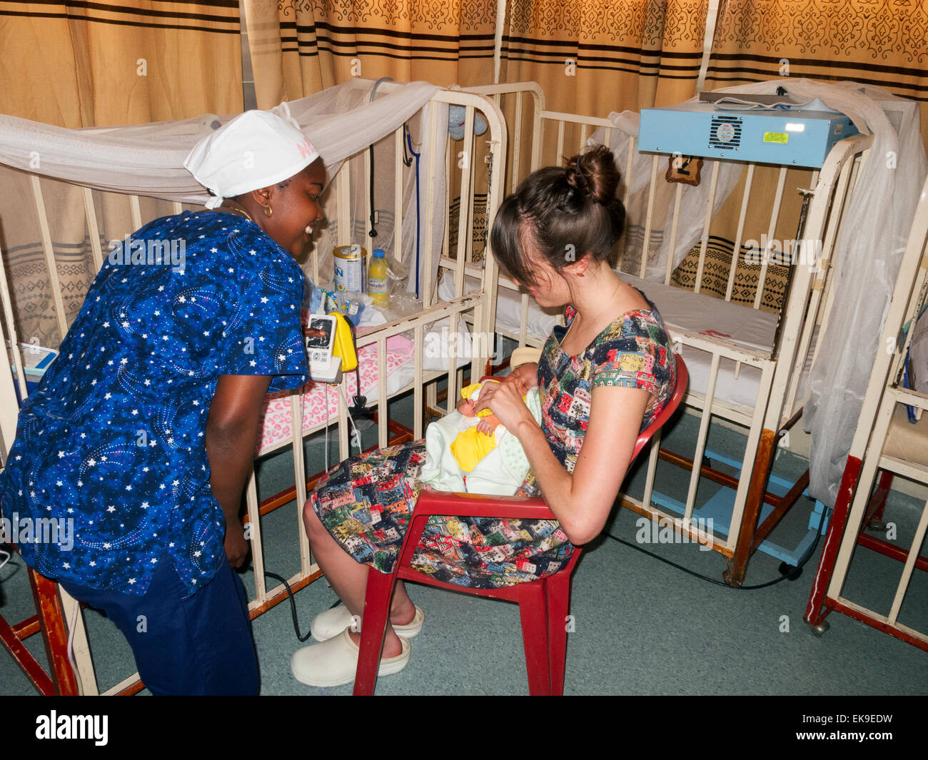 A congolese nurse and western health aid worker feeding a baby, Heal Africa Hospital; Goma, Democratic Republic - Stock Image