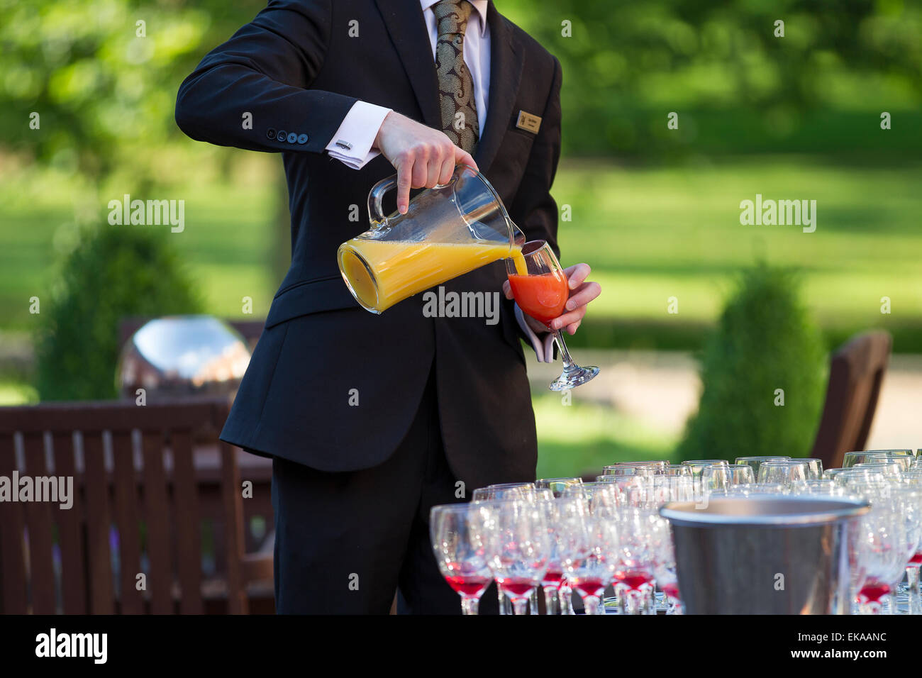 A waiter serves a non alcoholic fruit cocktail wearing a suit and tie - Stock Image