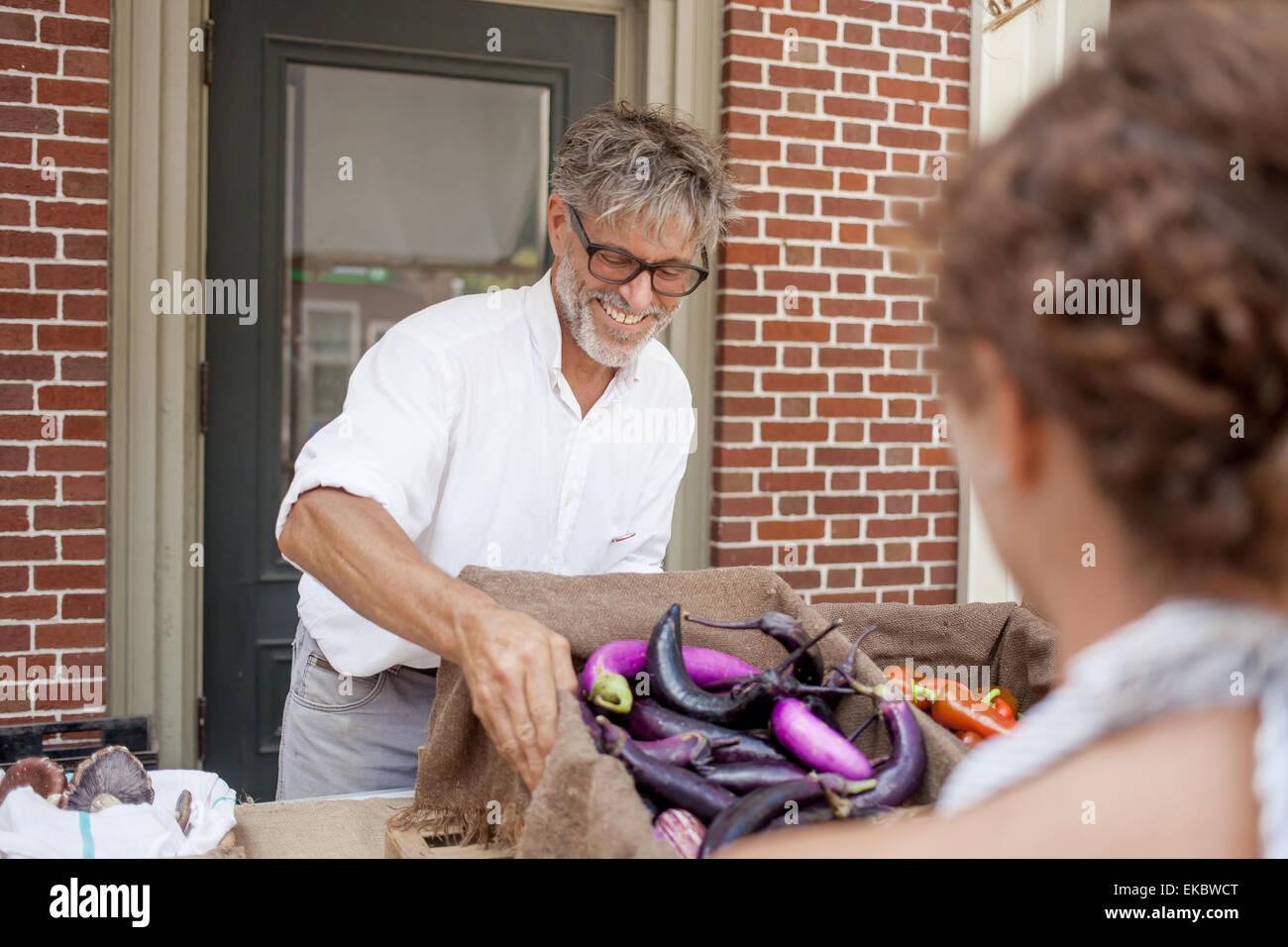 Farmer selling organic aubergines on stall - Stock Image