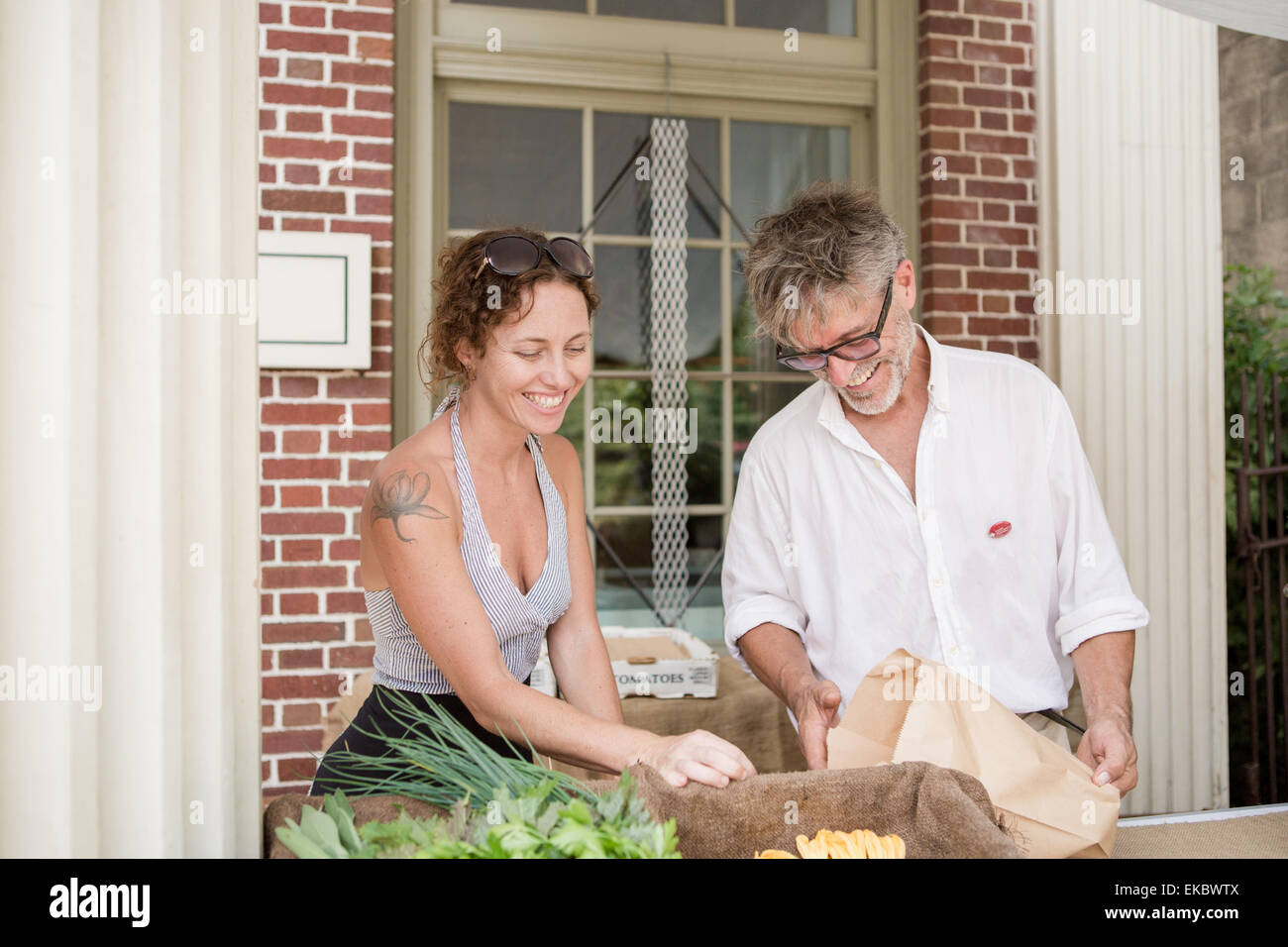 Farmers selling organic vegetables on stall outside store - Stock Image