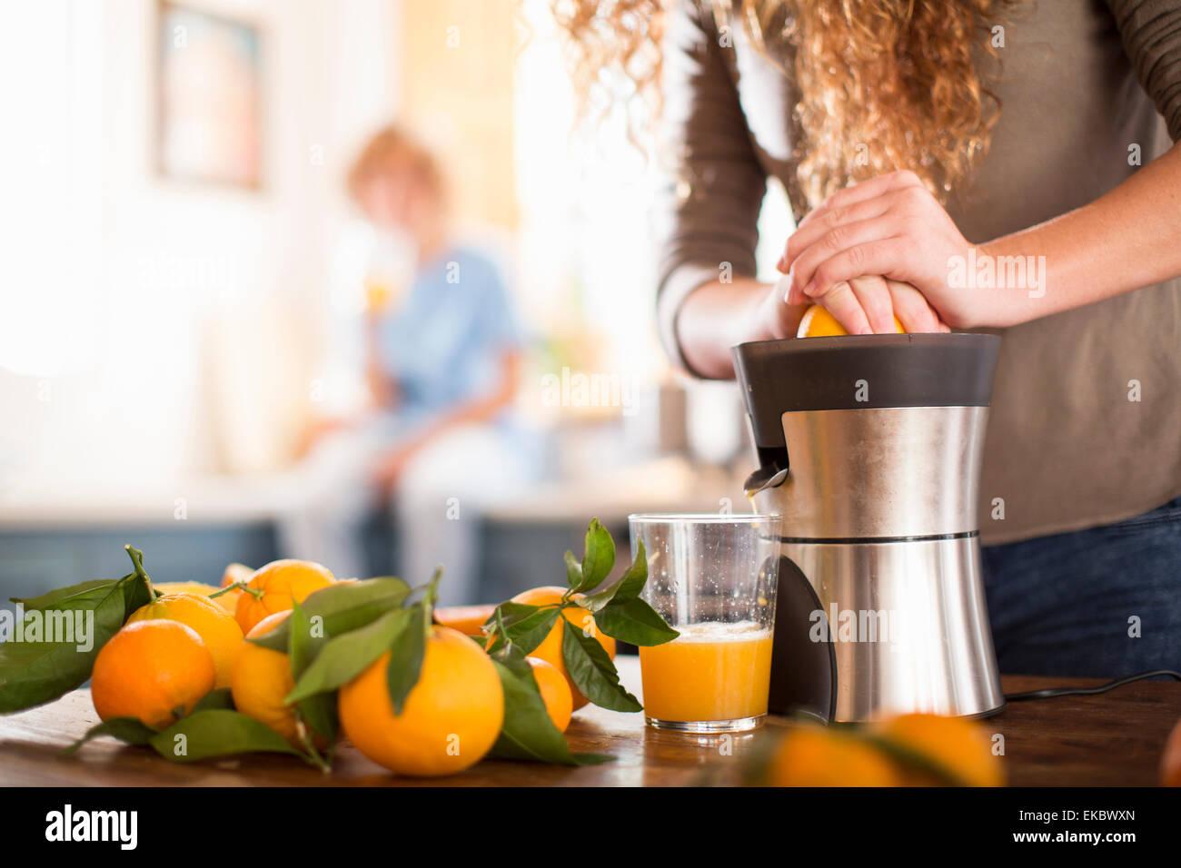 Teenage girl juicing orange in kitchen - Stock Image