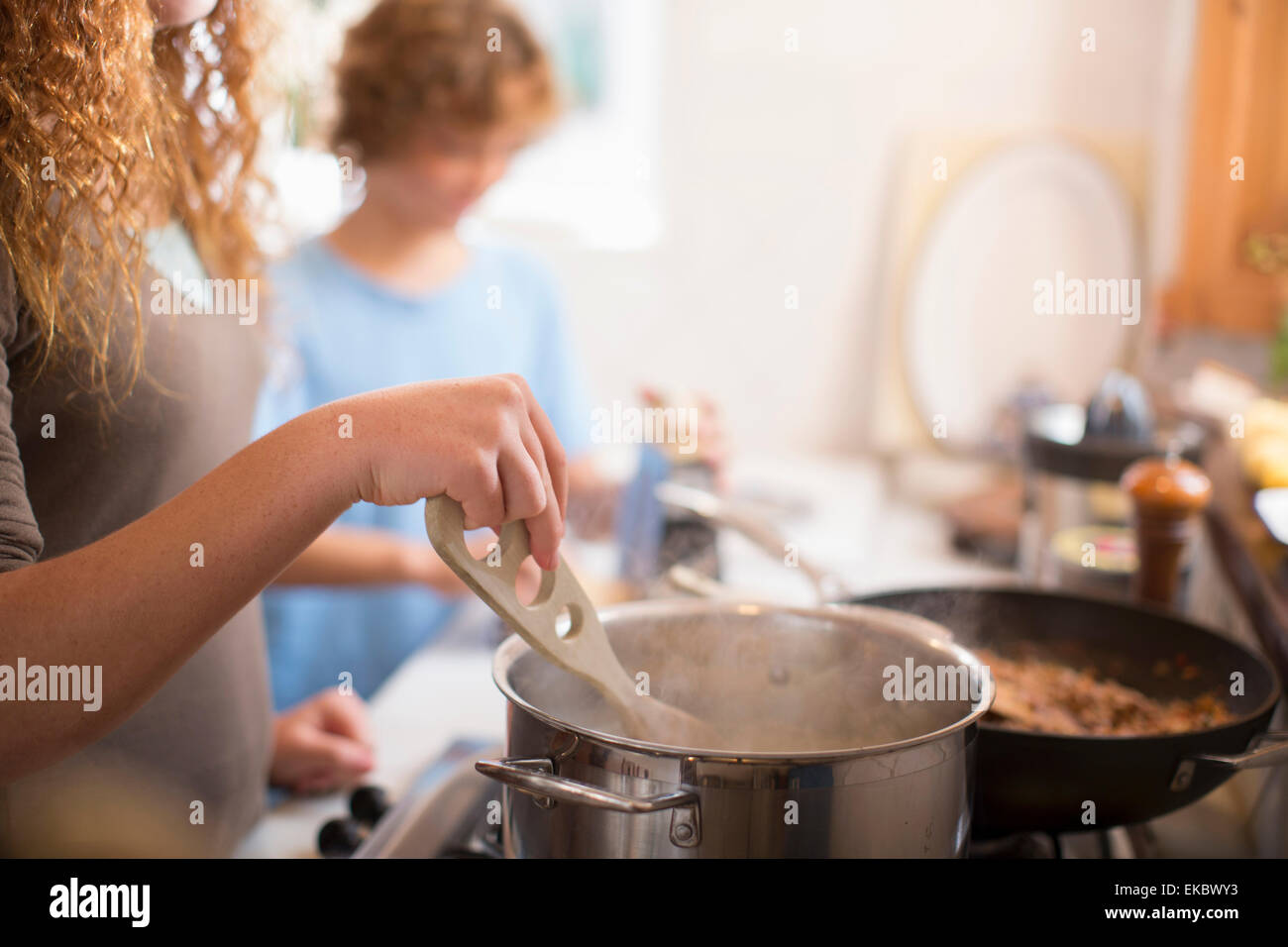 Siblings cooking in kitchen - Stock Image