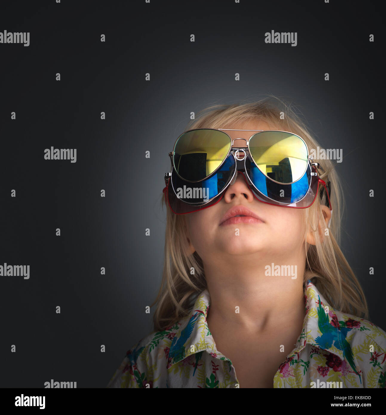 Portrait of young boy wearing 3 pairs of sunglasses - Stock Image