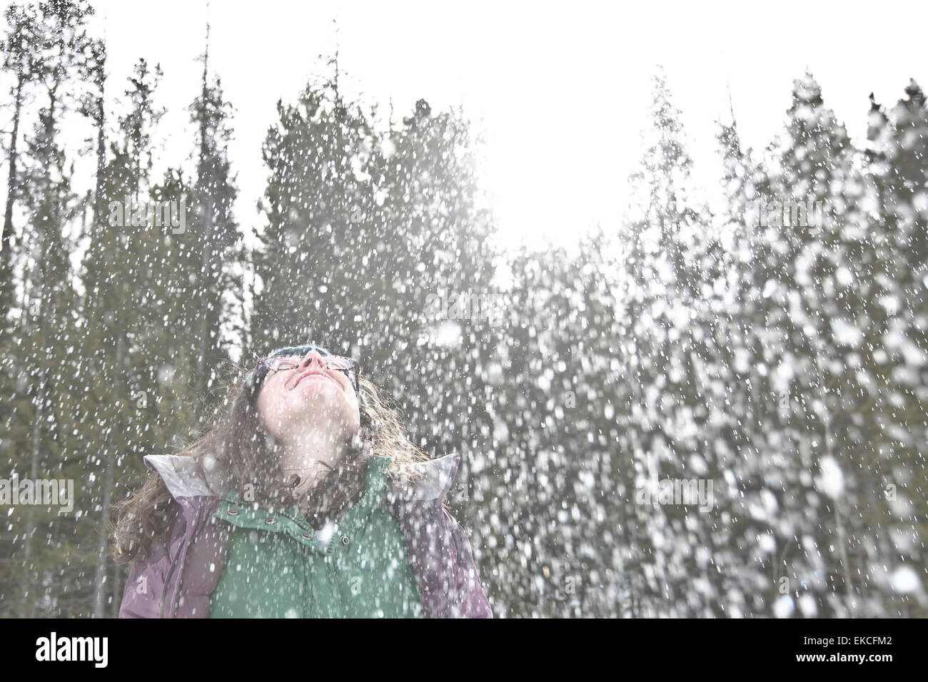 Woman in the snow throwing her head back and laughing - Stock Image