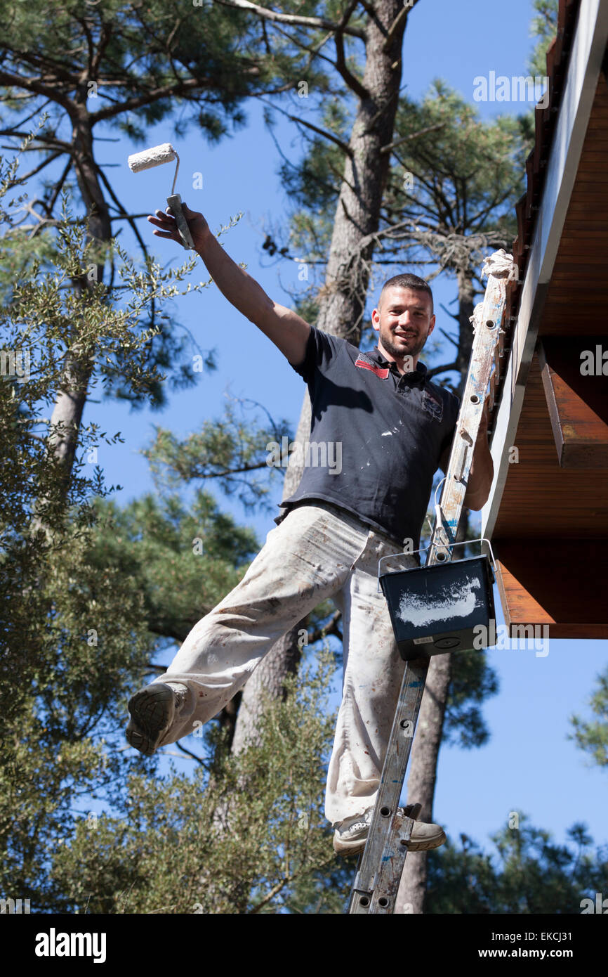 An overjoyed self-employed house painter at work on eaves (France). Peintre en bâtiment oeuvrant dans la joie - Stock Image