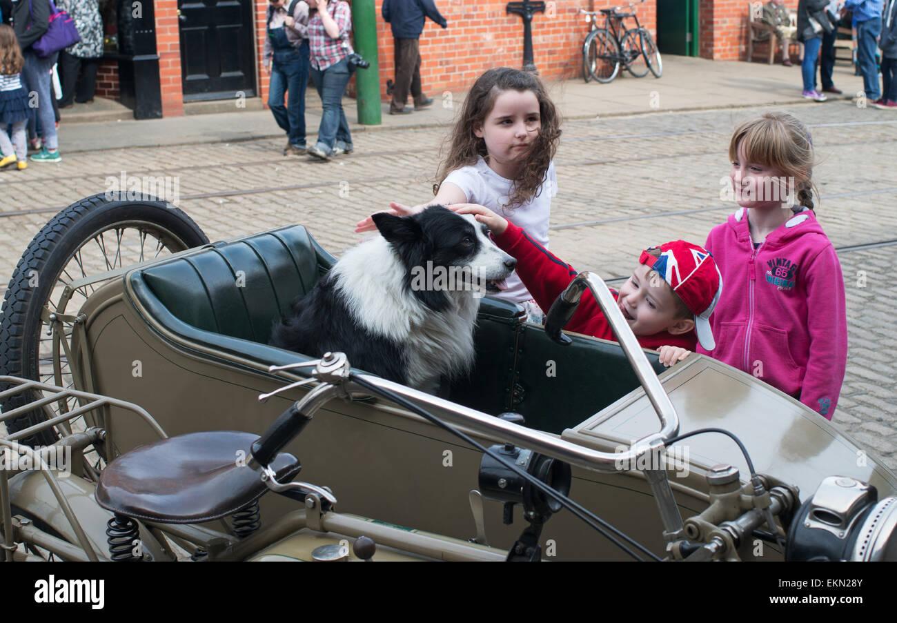 children-stroking-dog-in-motorcycle-side