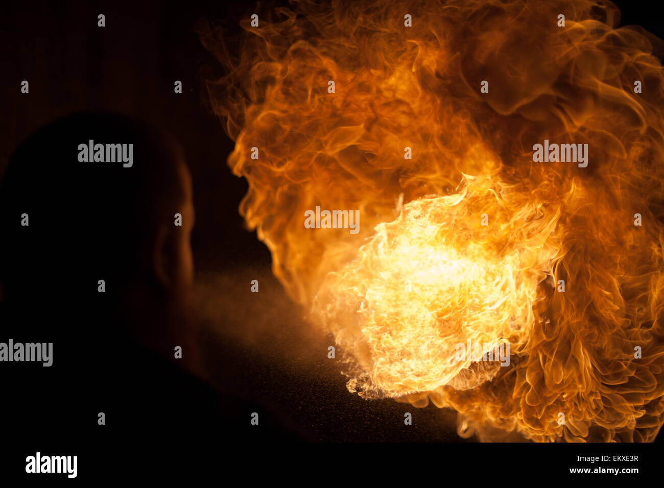 a fire breathe with a silhouetted performer figure - Stock Image