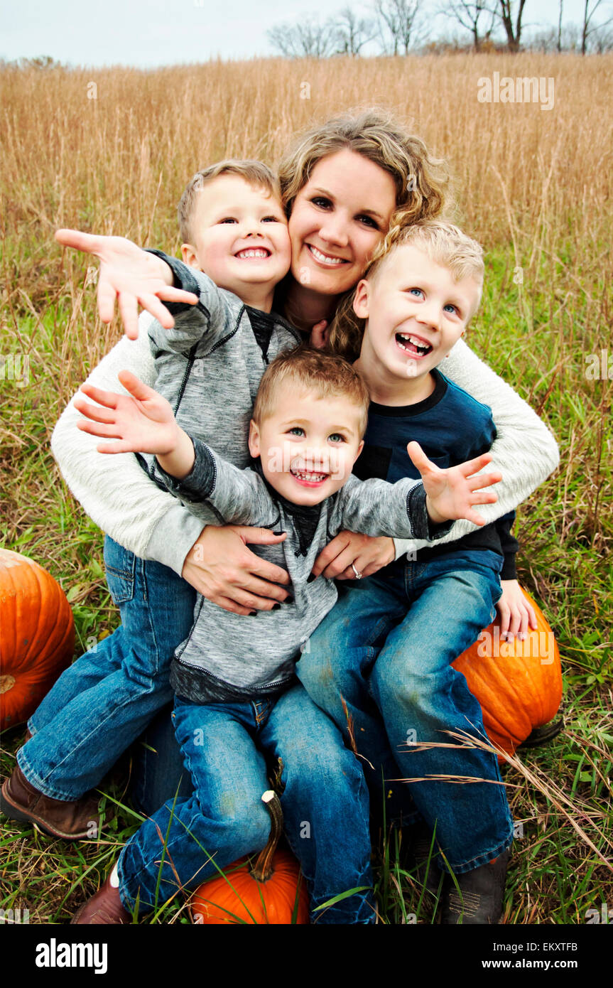 Mother holding three boys in her arms - Stock Image