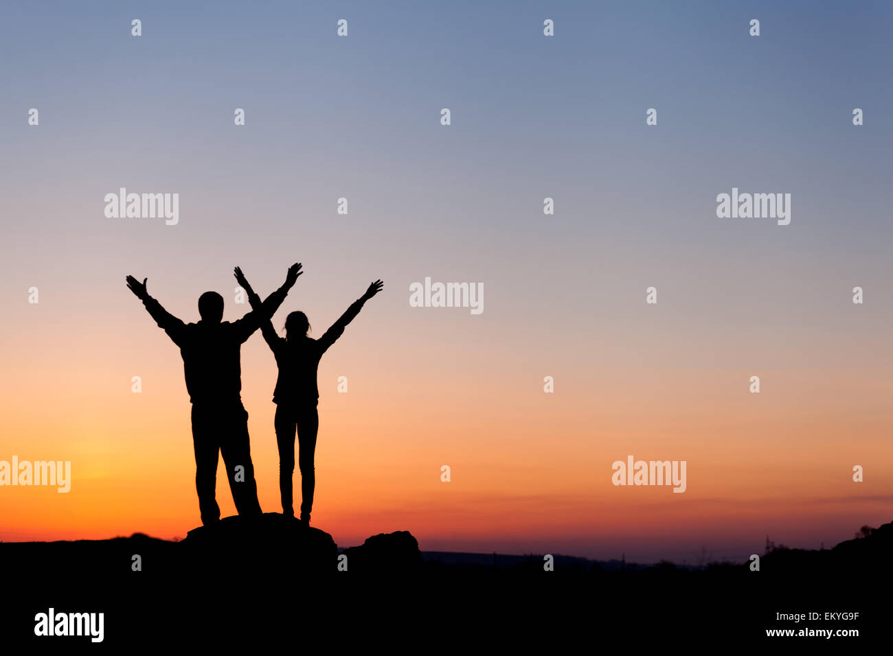 Silhouette of happiness family with arms raised up against beautiful colorful sky. Summer Sunset. Landscape - Stock Image