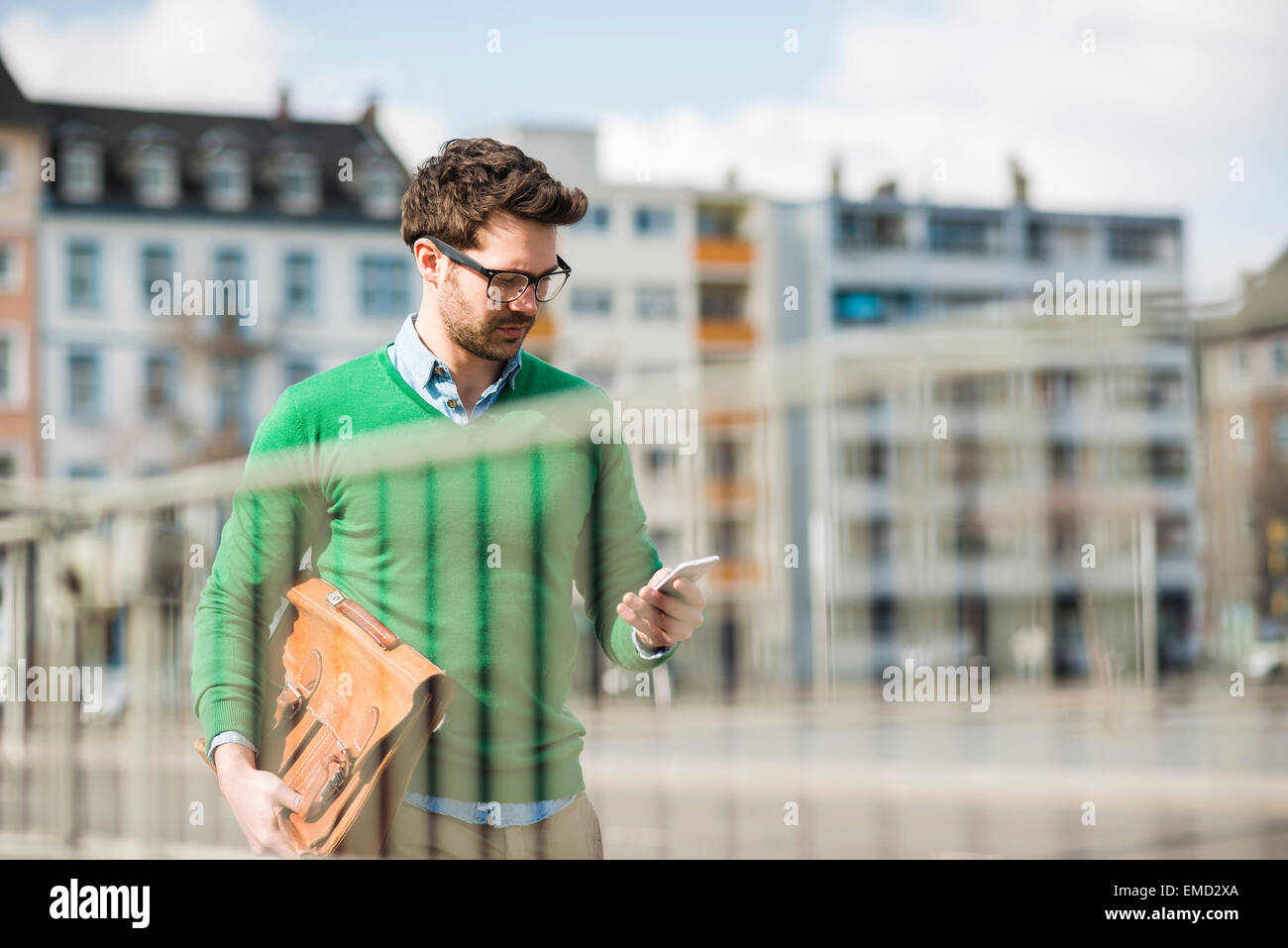 Man in green sweater carrying briefcase, reading text message - Stock Image
