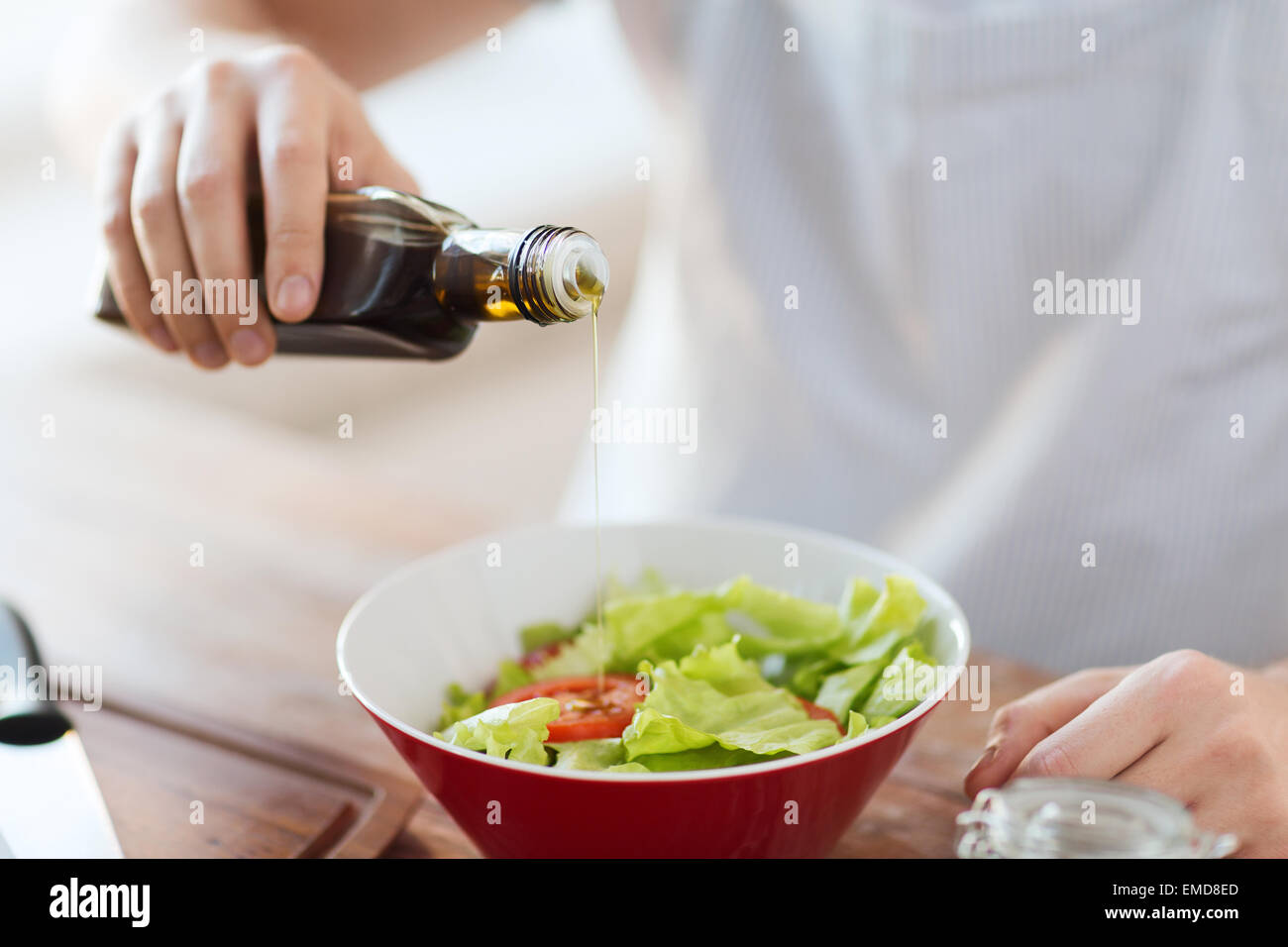 close up of male hands flavouring salad in a bowl - Stock Image