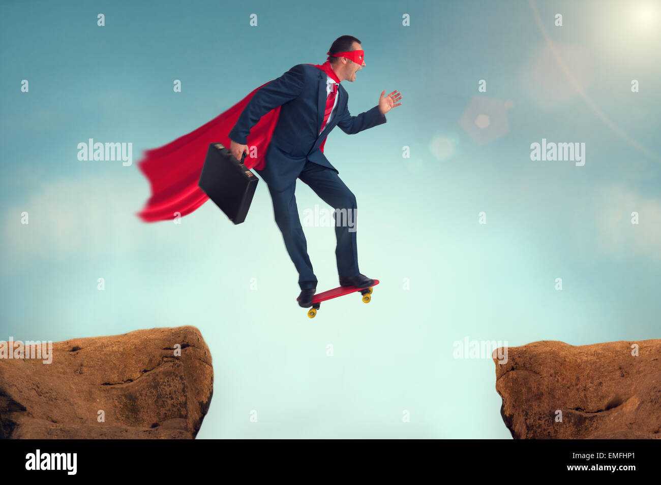 superhero businessman challenge making a risky leap of faith on a skateboard - Stock Image