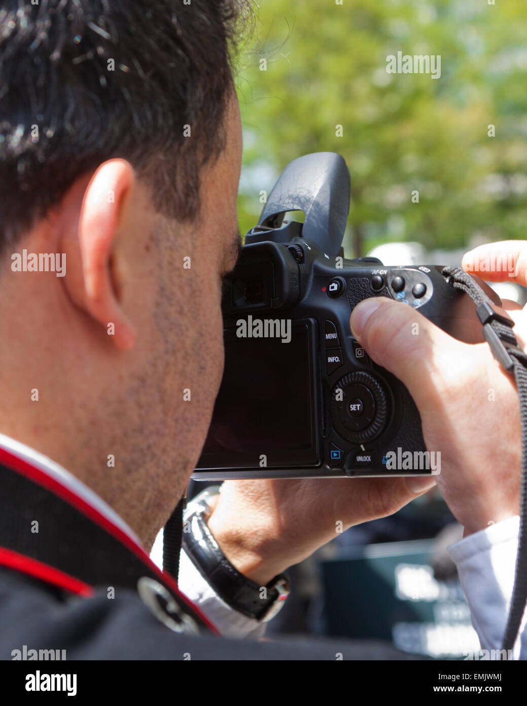 Man looking through viewfinder of dSLR camera - USA - Stock Image