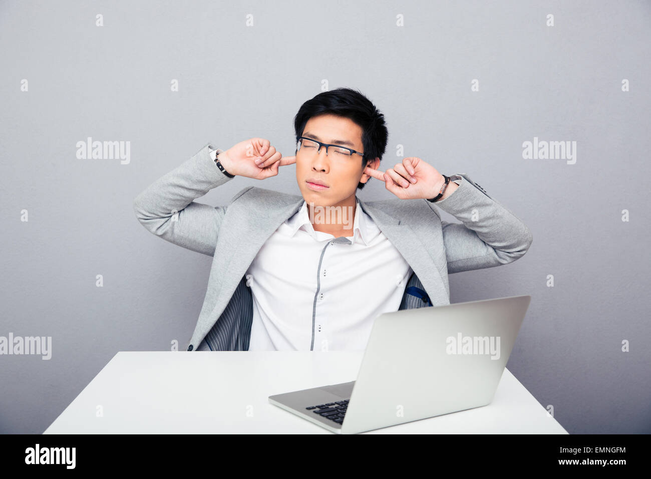 Handsome asian businessman sitting at the table and covering his ears over gray background - Stock Image