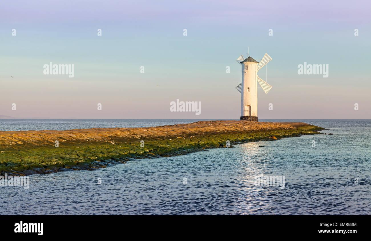 Sunrise over Baltic Sea coast, lighthouse in Swinoujscie, Poland. - Stock Image