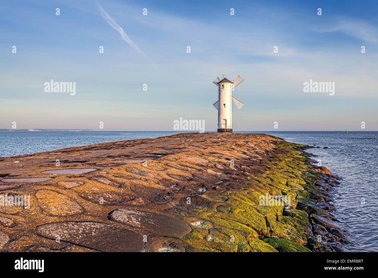 Vivid sunrise over pier and lighthouse in Swinoujscie, Poland. - Stock Image