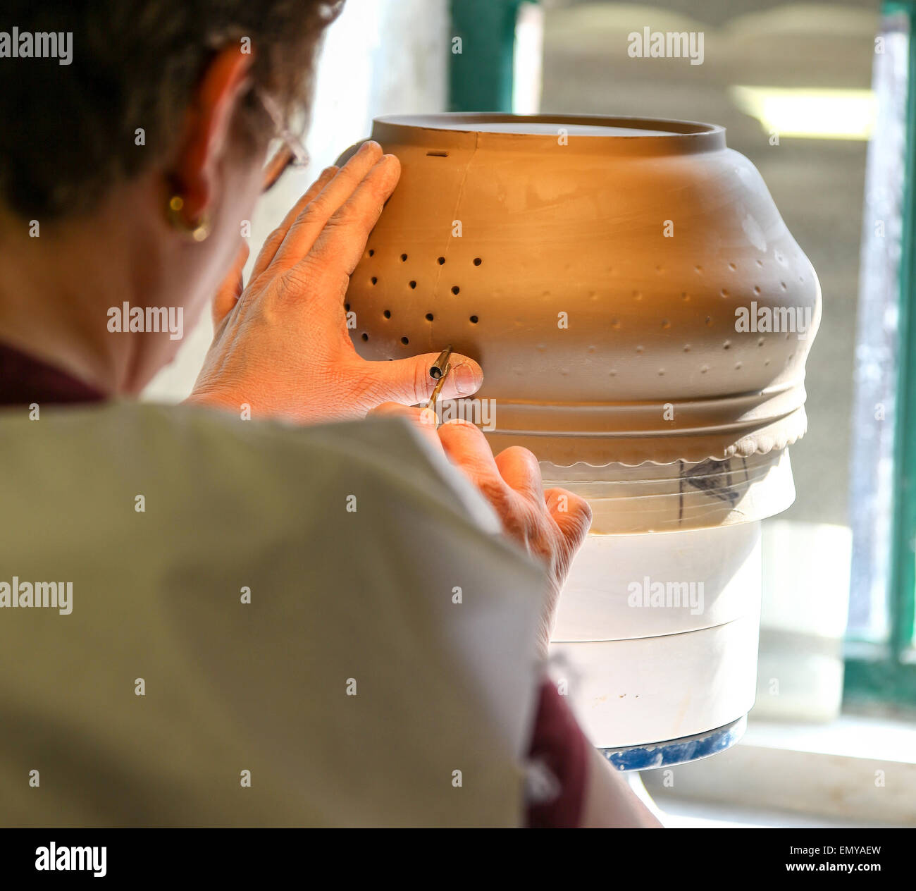 a-woman-hand-piercing-a-clay-pot-at-the-burleigh-middleport-pottery-EMYAEW.jpg