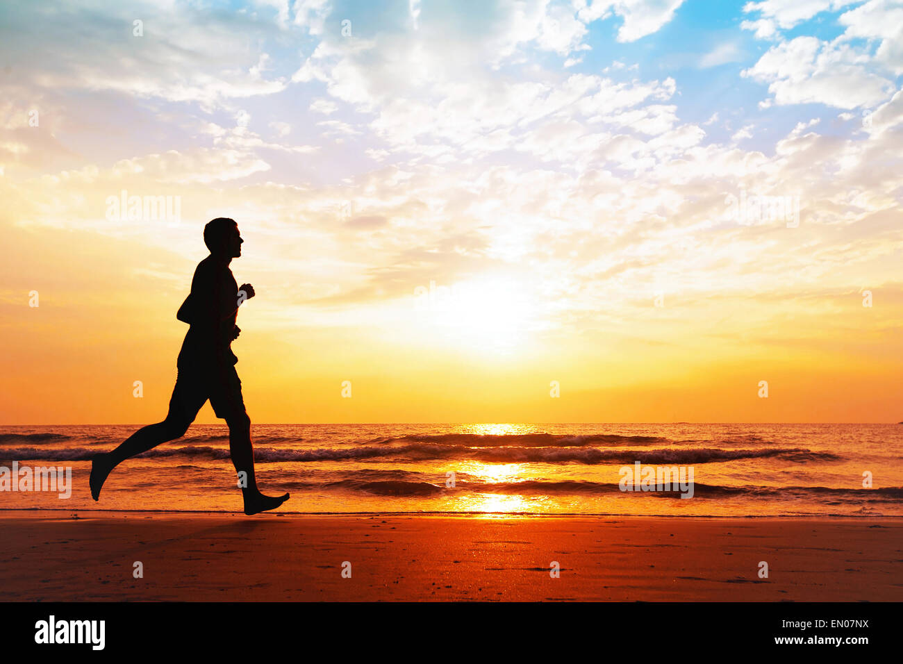 active healthy lifestyle, silhouette of man jogging on the beach - Stock Image