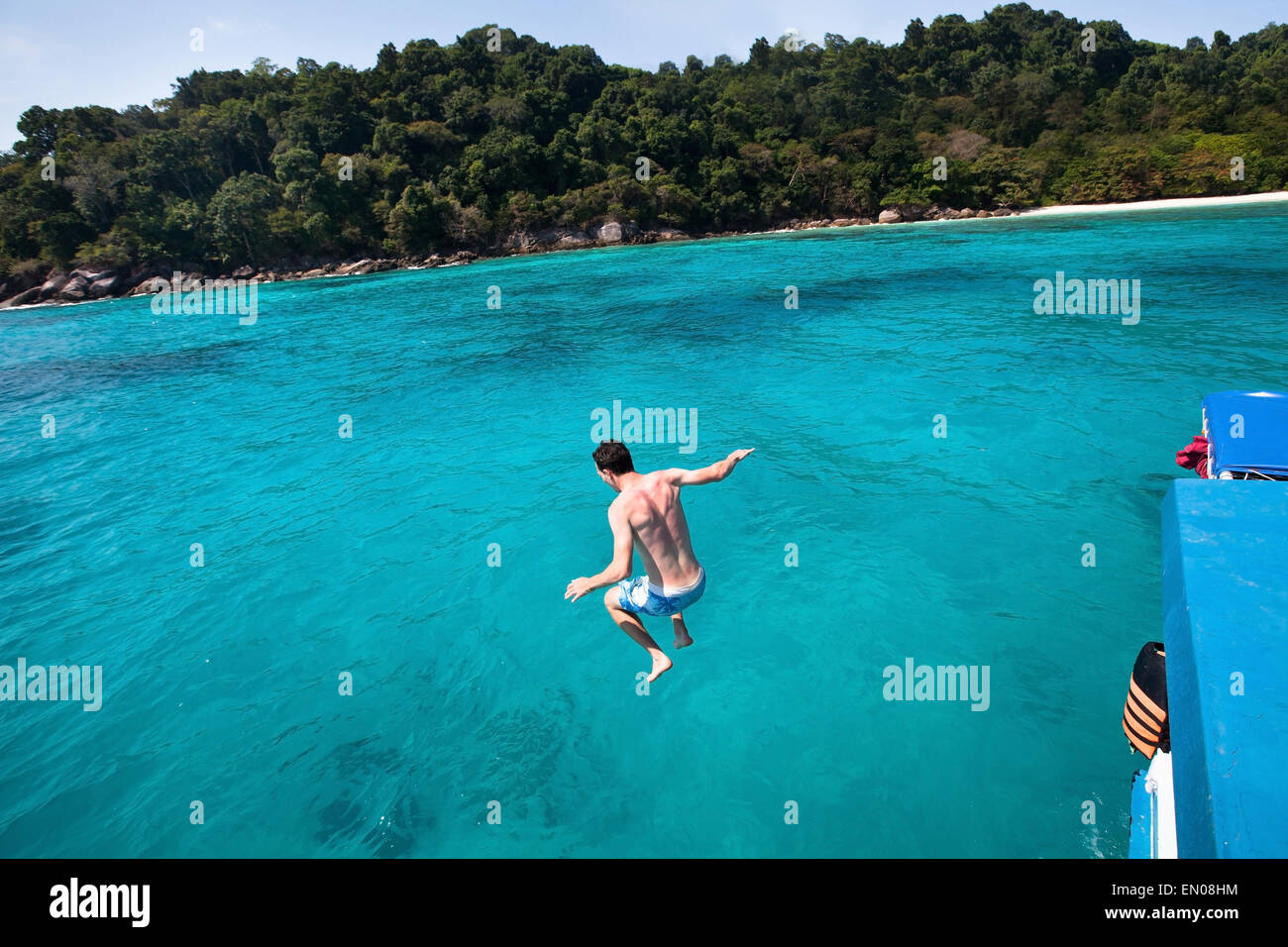 young man jumping to the sea from yacht near the beach of paradise island - Stock Image