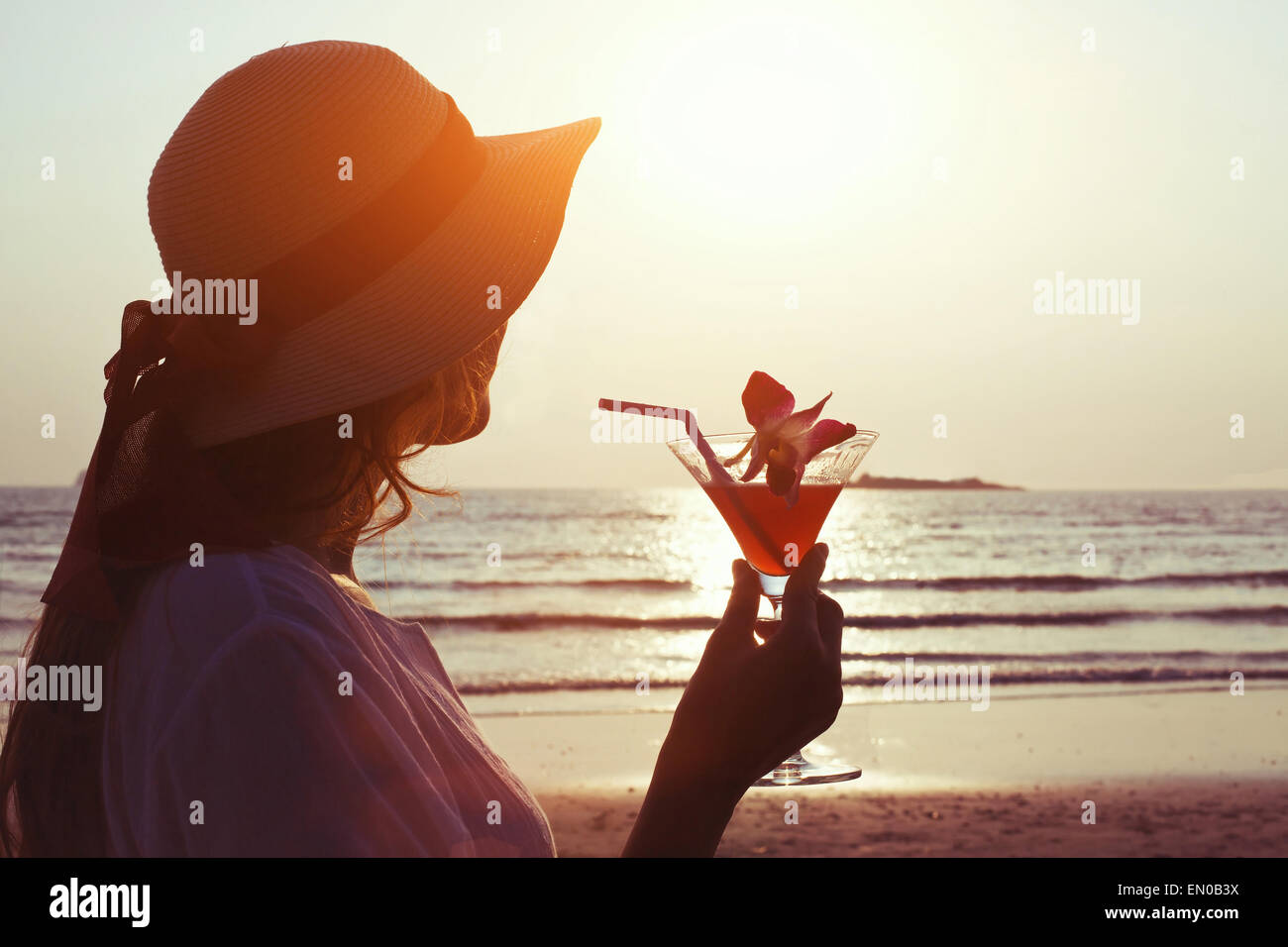 woman with cocktail at sunset beach - Stock Image