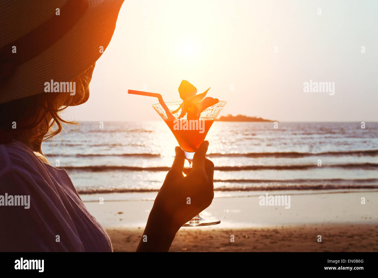 woman with cocktail on the beach - Stock Image