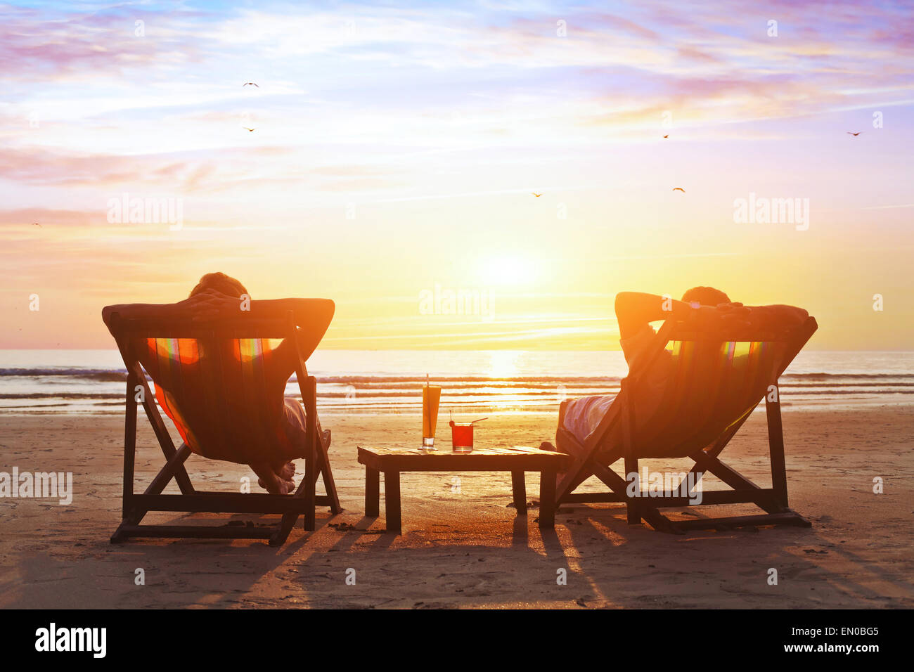 happy couple enjoy luxury sunset on the beach during summer vacations - Stock Image