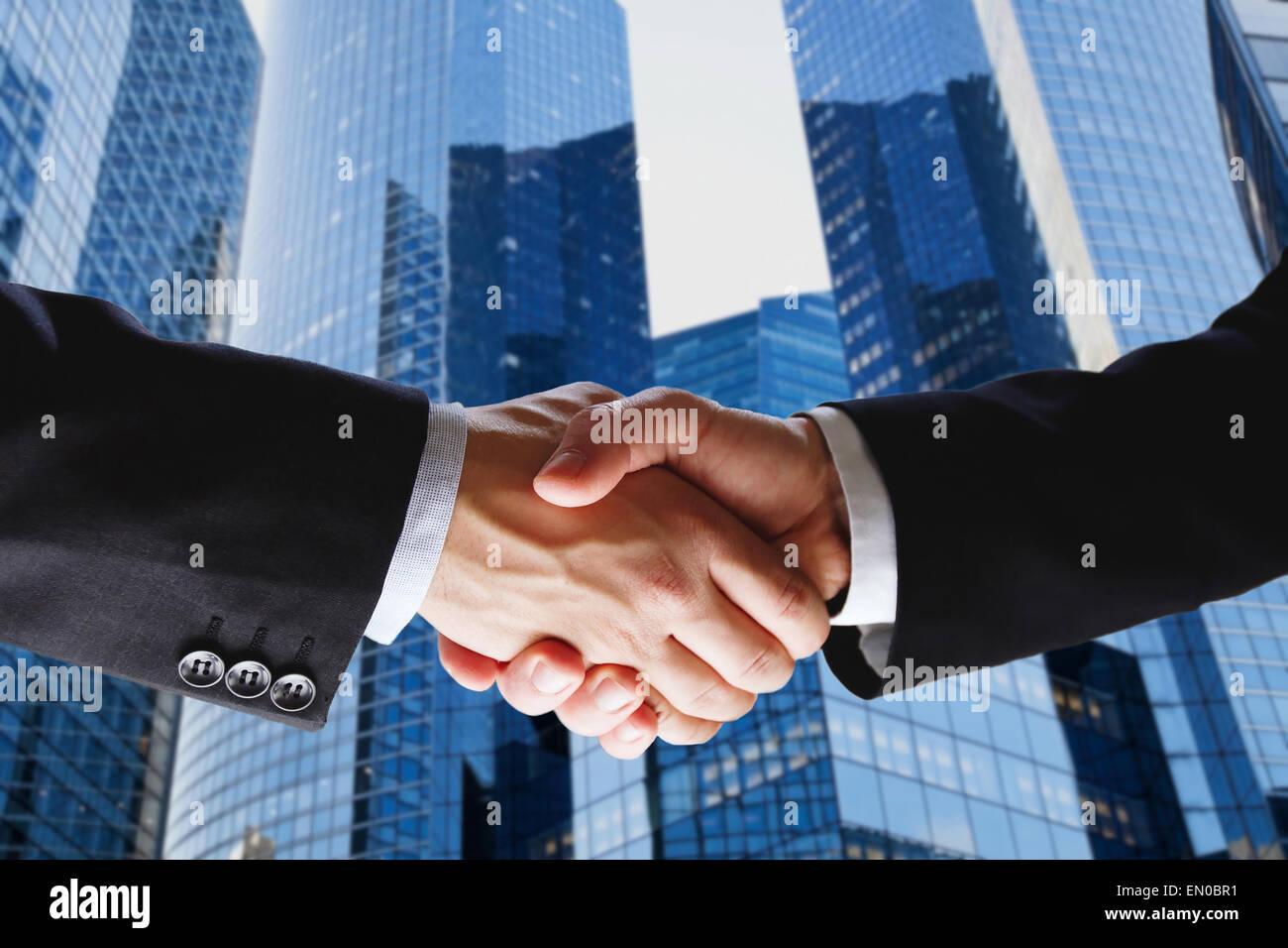business deal, handshake on modern blue background - Stock Image