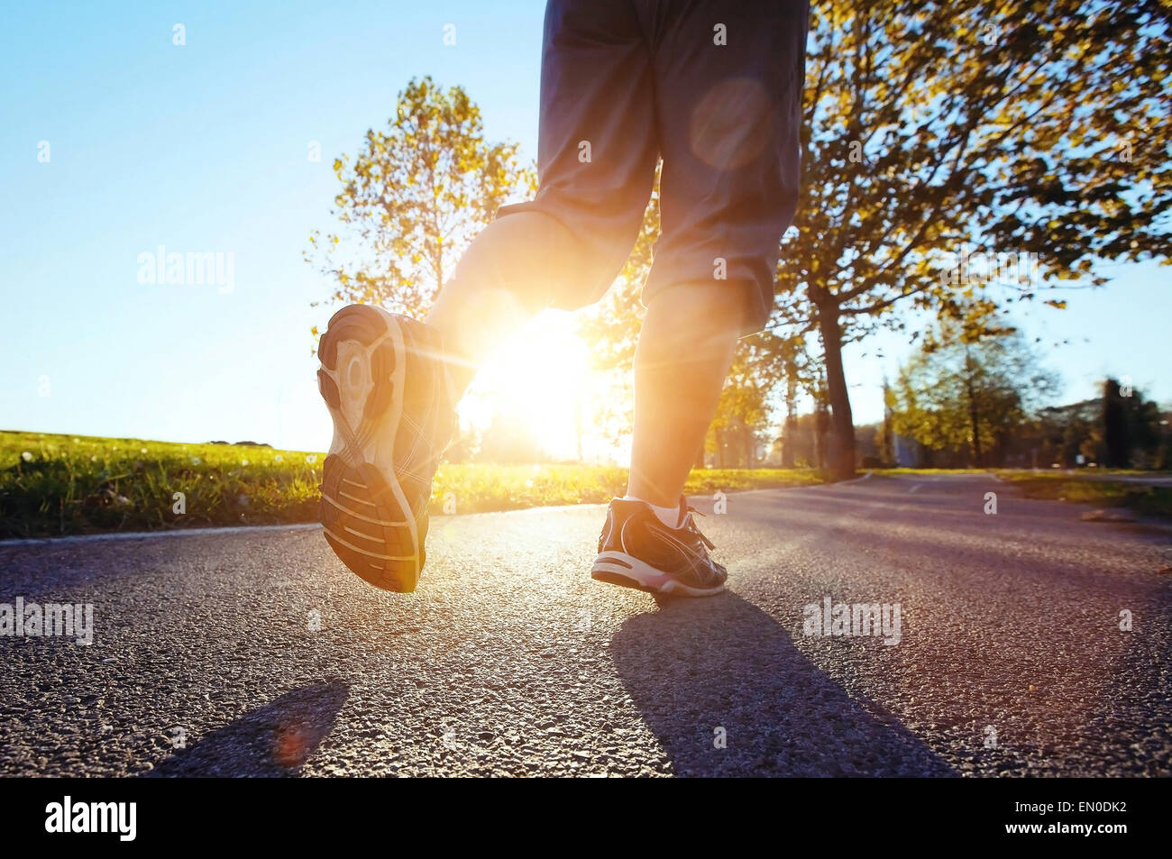 close up feet of runner at sunset - Stock Image