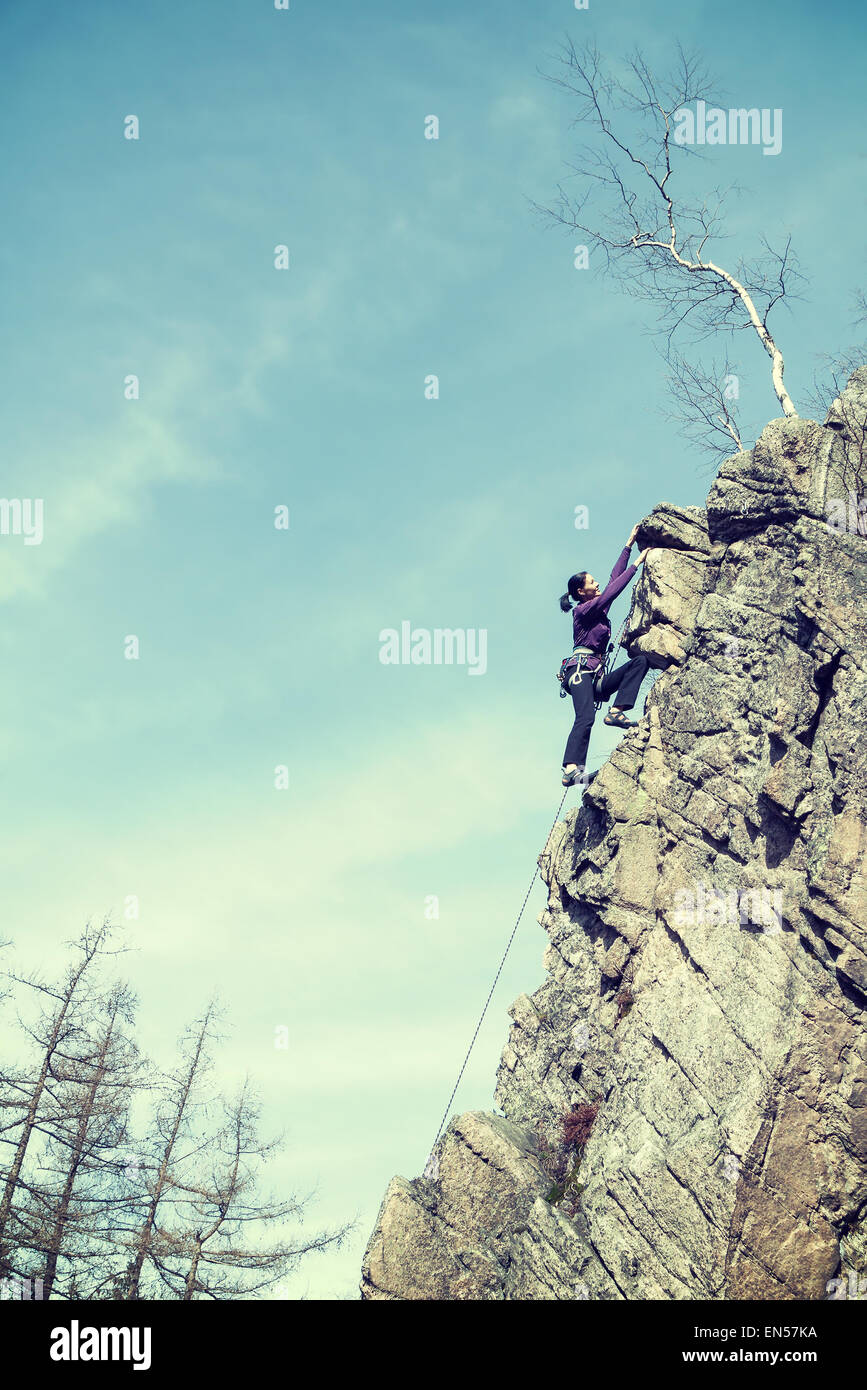 Retro filtered photo of a female rock climber, old grainy film effect. - Stock Image
