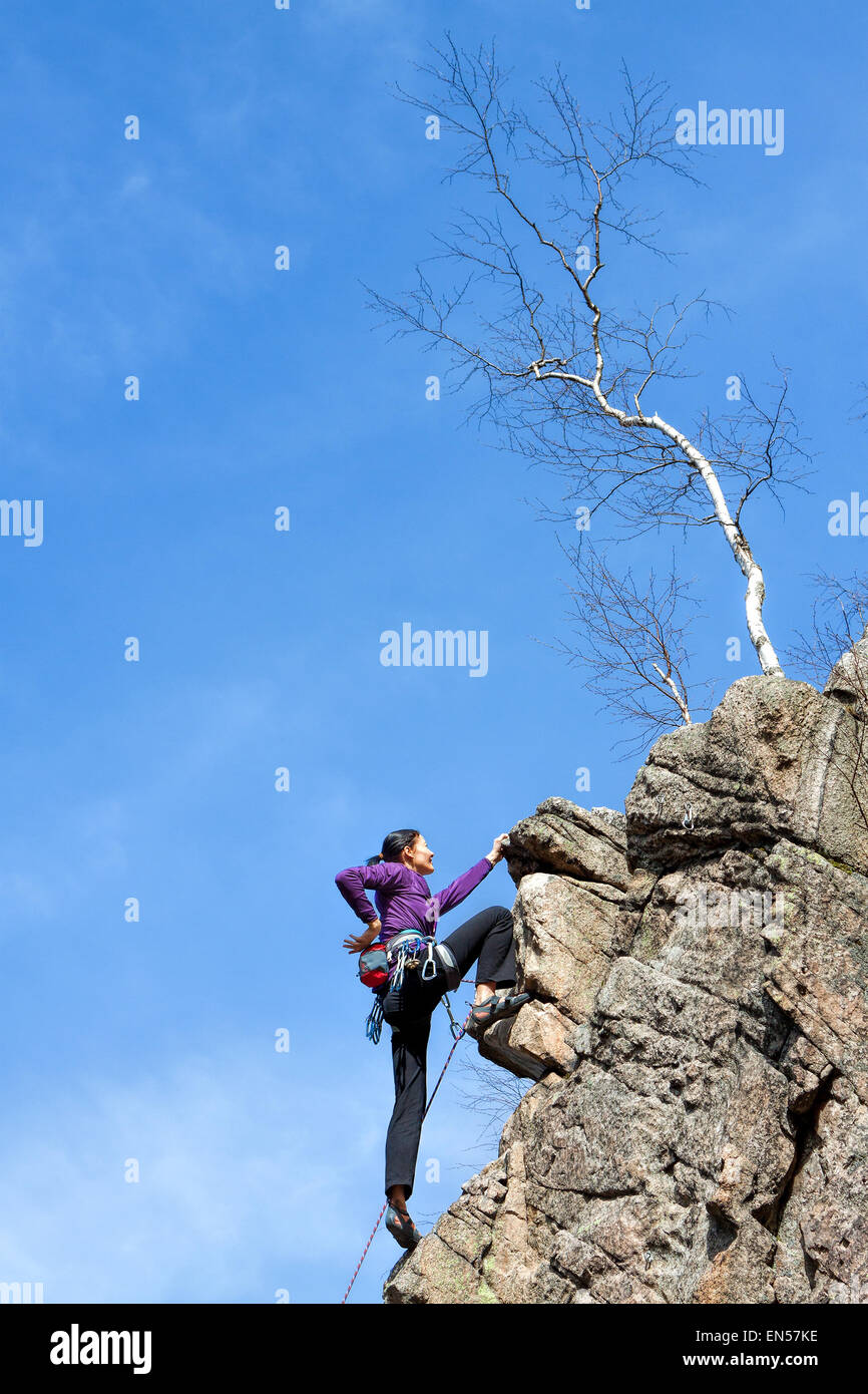 Female happy rock climber on a steep cliff. - Stock Image