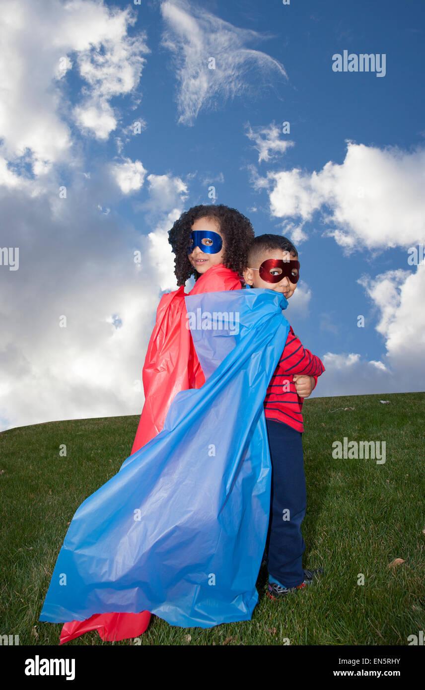 little boy and girl superheros against blue sky - Stock Image